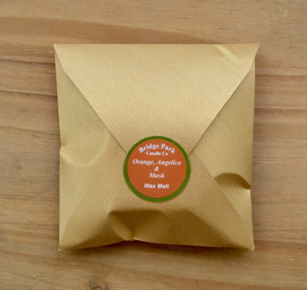Bridge Park Candle Company Orange, Angelica & Musk wax melt in a small gold envelope.