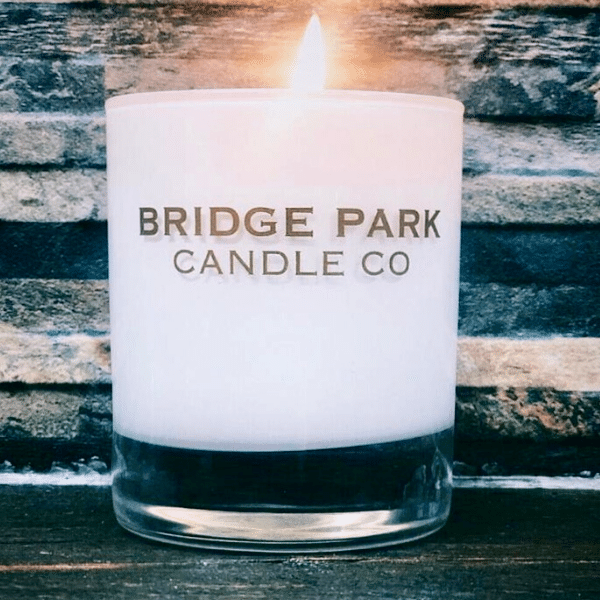 Bridge Park Candle Company lit candle with wood background