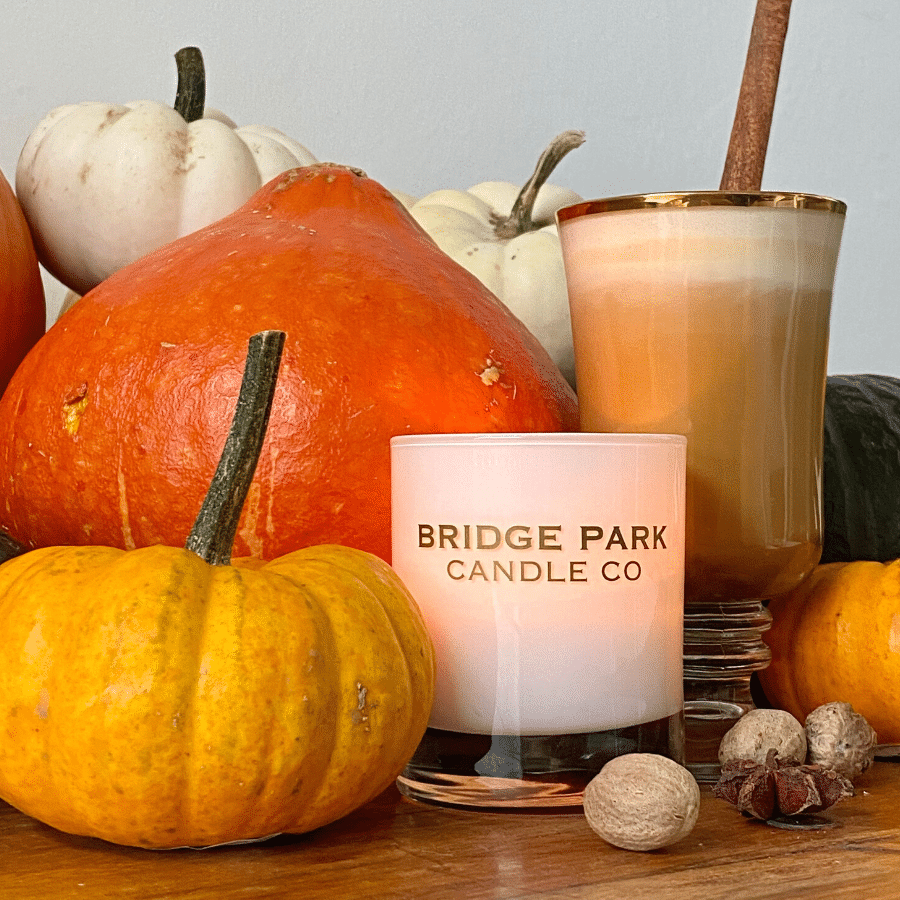 Bridge Park Candle Company Pumpkin Chai Latte candle surrounded by pumpkins & spices with a chai latte and a cinnamon stick