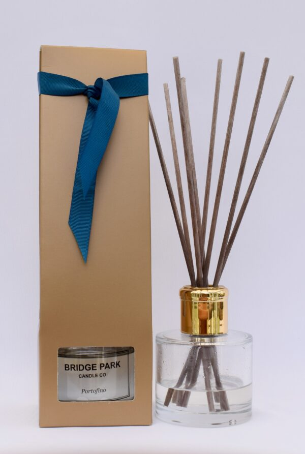 Bridge Park Candle Company Portofino Reed Diffuser next to a gold box and tied with a teal ribbon